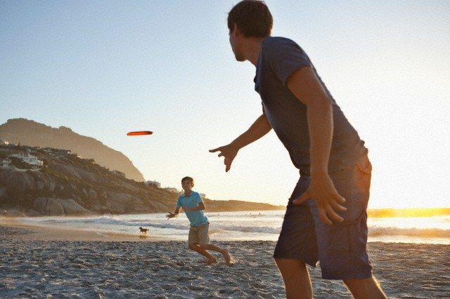 Father with son (7-9) playing frisbee on beach