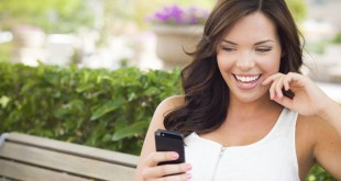 Attractive Smiling Young Adult Female Texting on Cell Phone Outdoors on a Bench.