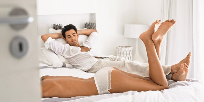 Man looking at his topless girlfriend lying on the bed